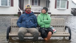 Stephen Eren and Alex Crooks pose on a bench amid flooding