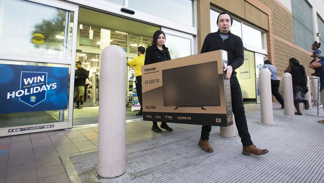 "Joseph Frato and Letizia Dunlap of Phoenix leave with a 55"" Toshiba LED TV on Thanksgiving 2015 at the early opening of Best Buy on Camelback Road in Phoenix."