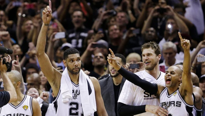 The San Antonio Spurs Tony Parker (9), Tim Duncan (21), Matt Bonner, and Patty Mills (8) celebrate in the final moments at Game 5 of the NBA basketball finals against the Miami Heat on Sunday, June 15, 2014, in San Antonio. The Spurs won the NBA championship 104-87.
