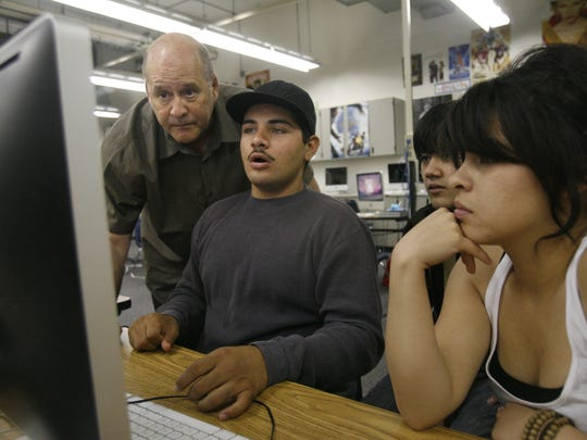 David Vogel (left) looks over the work of Cathedral City High School students Juan Ramirez (from left), Christian Alzaga and Laura Ruiz during class at Cathedral City High School's DATA program in May of 2009.