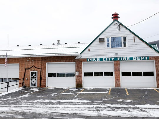 Black bunting hangs over the Pine City Volunteer Fire Department's door as flags fly at half-staff in memory of Tim Hassen, who died Wednesday. Hassen was a former chief for the department and worked at Ernie Davis Academy as the assistant principal.