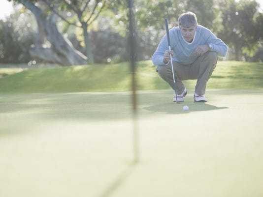 Man assessing play on putting green