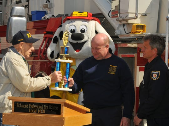 Retired Richmond Fire Department Capt. Mel Ponder, left, who inspired the Cuffs and Ladders Blood Drive presents Richmond firefighters Harold Erbse, Curt Bane and Chuck Powell with a trophy for winning the first blood drive between police officers and fire fighters during a presentation on April 3, 2013, at Richmond Fire House No. 1.