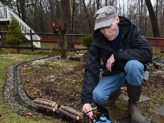 Thomas Murphy adjusts a tank engine on his garden railway in the backyard of his Hyde Park home.