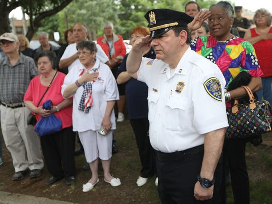 Clifton Police Capt. Chris Stabile and Fannie Ballard, of Hackesack, salute the flag during the dedication service for the John E. Biegel Flag Barn, in Clifton, Sunday, June 10, 2018.