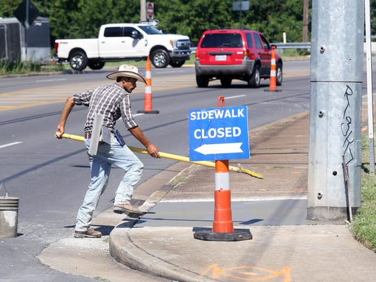A worker repairs sidewalks on Cleveland Street on July