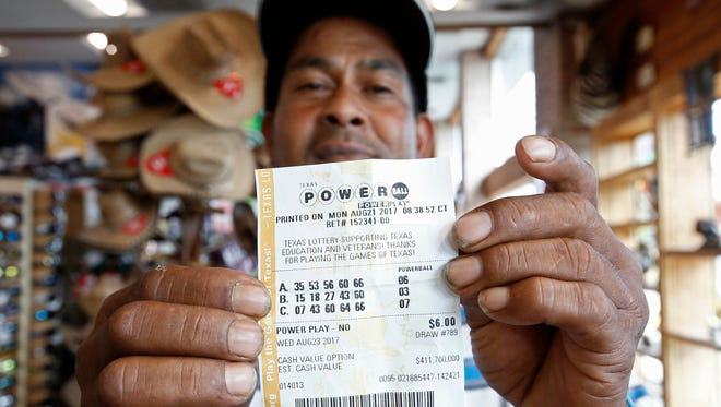 This man in Dallas TX holds up a Powerball lottery ticket he purchased at a gas station Aug. 23, 2017.