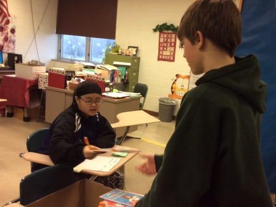 Freshman Ben Rowerdink donates books while Pang Yang