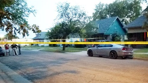 """In this Thursday photo police tape surrounds a gray car outside a Wichita, Kan., where a 10-month-old girl died after being left inside a hot car. Authorities said today they have arrested the girl's foster parent on suspicion of aggravated endangerment but charges have not been filed. Police said the man had """"somehow forgotten"""" leaving the girl in the back seat after picking her up from the baby sitter late Thursday afternoon."""