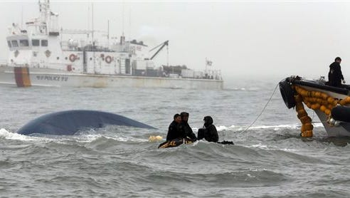 South Korean Navy personnel try to search missing passengers aboard the sunken ferry Sewol in the water off the southern coast near Jindo, South Korea, Friday, April 18, 2014. Investigations into South Korea's ferry disaster focused on the sharp turn it took just before it started listing and on the possibility that a quicker evacuation order by the captain could have saved lives, officials said Friday, as rescuers scrambled to find some 270 people still missing and feared dead. (AP Photo/Yonhap) KOREA OUT