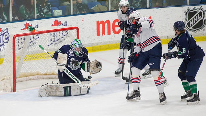 Plymouth goalie Alec Nedeljkovic makes one of his 57 stops Saturday against Oshawa. At right for the Whalers is defenseman Mitch Jones.
