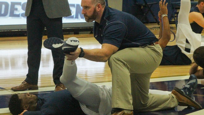 Uniontown native Tim Campbell helps a University of Akron basketball player stretch before a game last season.
