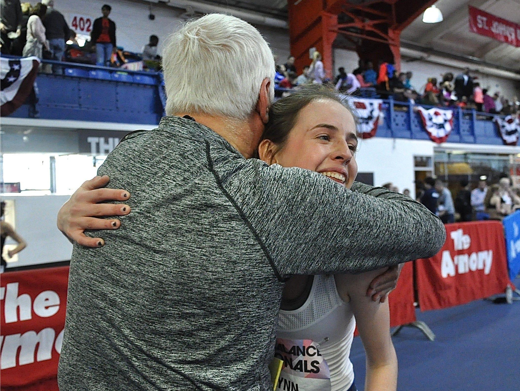 Ursuline coach Jan Mitchell hugs senior Anna Flynn after the girls 4x1 mile relay in which Ursuline finished third..