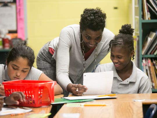Tatiana Brown, right, reacts as her teacher Tamara Joy Hunter reads her essay on Wednesday at Franklin Park Magnet School in Fort Myers. Brown had been struggling with writing and was excited to share the paper with Hunter.