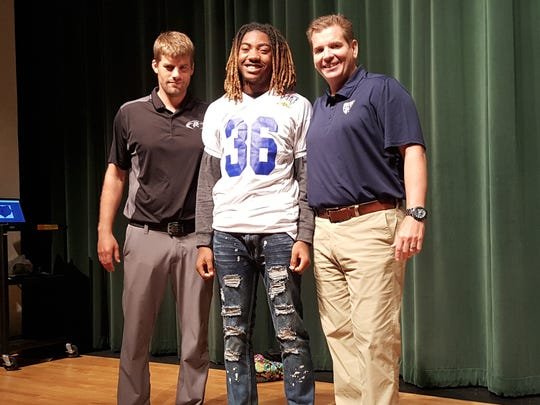 Palmetto Ridge football player Kamonte Grimes (center) poses with coach Chris Toukonen and All-American Games vice president Steve Quinn after Grimes was named to the Freshman All-American Bowl during a ceremony at the school on Oct. 25, 2017.