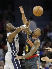 Piston Reggie Jackson passes the ball under pressure from Atlanta's Jeff Teague during the first half of the Hawks' 112-95 romp Saturday.