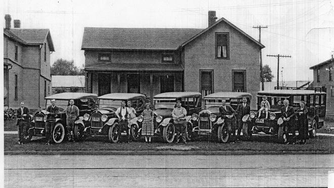 """Vintage automobiles with their proud owners and families pose in front of this house on West State in the 1920s, when trolley tracks still ran down the center of the Fremont street.  Notice the early """"station wagon"""" van at the right.  The house still stands at 1413 W. State St. today."""