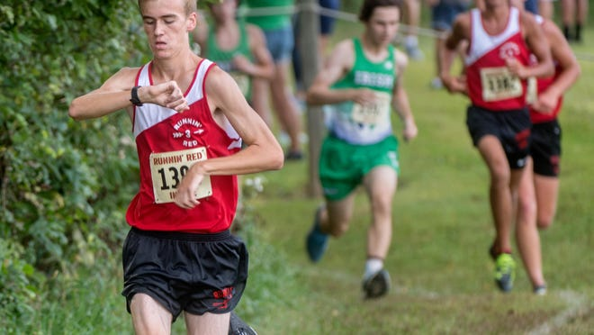 Metamora's Ian O'Laughlin checks his time as he nears the mile mark ahead of the pack during a cross country meet Wednesday, Sept. 3, 2020 at Black Partridge Park in Metamora. O'Laughlin won the race with a time of 15:43.29, leading the Redbirds to a team victory as well.