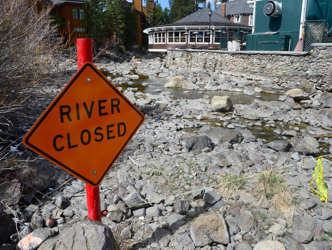 A 'River Closed' sign is posted on the Truckee River