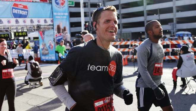 Brian Flemming, center, 32, of Canton runs past the finish line after completing the half marathon during the 37th annual Detroit Free Press/Talmer Bank Marathon on Oct. 19. Flemming finished his first half marathon after losing almost 400 pounds.