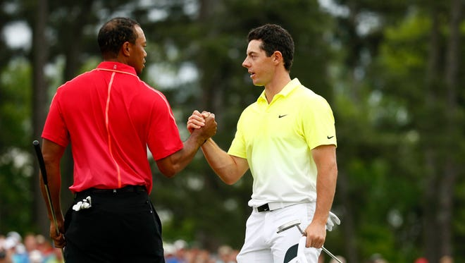 Rory McIlroy (right) and Tiger Woods (left) shake hands after completing the final round of The Masters golf tournament at Augusta National Golf Club.