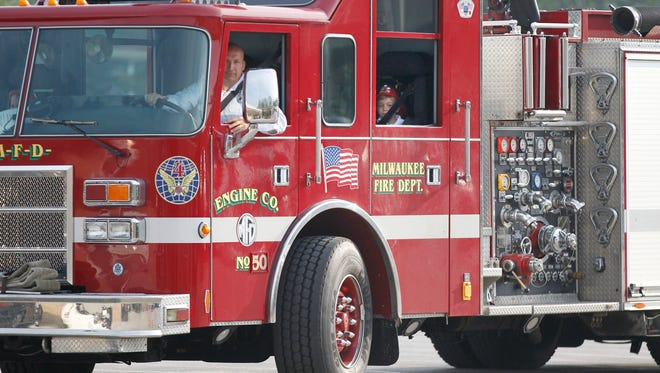 "standalone - firetruck  - with gallery - St. John Vianney Catholic School kindergartener Baron Reuter, (rear window) 5, is seen riding in a Milwaukee Fire Department firetruck driven by firefighter Mike Ball, as the truck rolls into the lot at St. John Vianney Catholic School in Brookfield. Reuter's parents, Bart and Carrie Reuter of Brookfield, had the winning bid of at a charity auction for the Basilica of St. Josaphat in Milwaukee last December, that allowed their son to ride to school in the firetruck. In addition to the charitable advantage of events like this, Milwaukee Fire Chief Mark Rohlfing explained that having firefighters in the public eye in non-emergency situations builds the relationship with the community. ""Whenever we can get a firetruck in a positive situation, it's a good thing.""   Monday, May 20, 2013. Photo by Mike De Sisti / MDESISTI@JOURNALSENTINEL.COM"