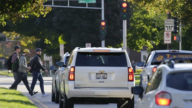 Traffic stops Tuesday for pedestrians as they use a marked crosswalk along College Avenue in front of Lawrence University in Appleton.