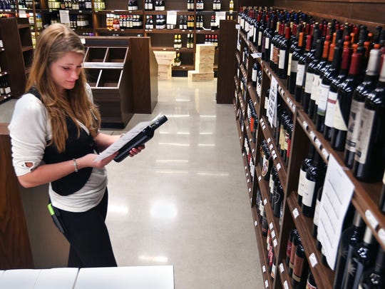 Market District employee Juli Boone stocks wines in