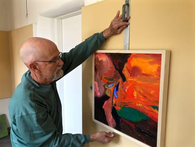 Exhibit designer Roger Conrad hangs a painting inspired