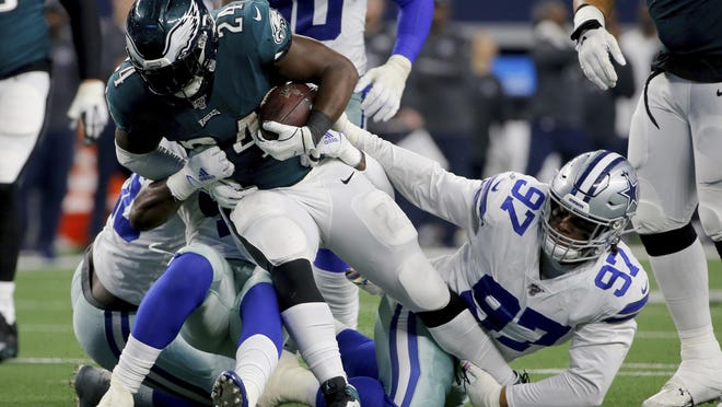 Philadelphia Eagles running back Jordan Howard attempts to break through a tackle by Dallas Cowboys' Trysten Hill.