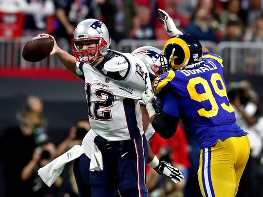 Aaron Donald, right, shown pressuring Tom Brady in the Super Bowl, will be present at the start of the Rams camp after two offseasons of contract issues.