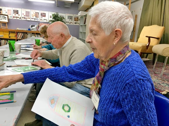 Renee Buttweiler holds artwork she created in Art Sparks, an art program designed for people with memory loss and their care providers, at the Paramount Center for the Arts earlier this year.