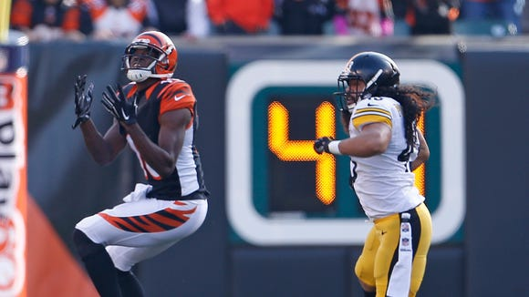 Cincinnati Bengals wide receiver A.J. Green (18) hauls in a long pass as he is defended by Pittsburgh Steelers strong safety Troy Polamalu (43) during the second quarter of their game played at Paul Brown Stadium in Cincinnati, Ohio Sunday December  7, 2014. The play set-up the Bengals first Touchdown. The Enquirer/Gary Landers
