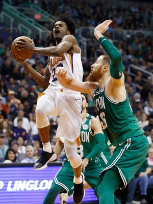 Phoenix Suns guard Josh Jackson, left, drives past Boston Celtics center Aron Baynes, right, during the second half of an NBA basketball game, Monday, March 26, 2018, in Phoenix. The Celtics defeated the Suns 102-94.