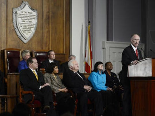 Gov. Robert Bentley delivers the State of the State speech on Jan. 14, 2014.  Seated beneath the plaque (l to r): Senate President Pro Tem Del Marsh, R-Anniston; Lt. Gov. Kay Ivey and House Speaker Mike Hubbard, R-Auburn.