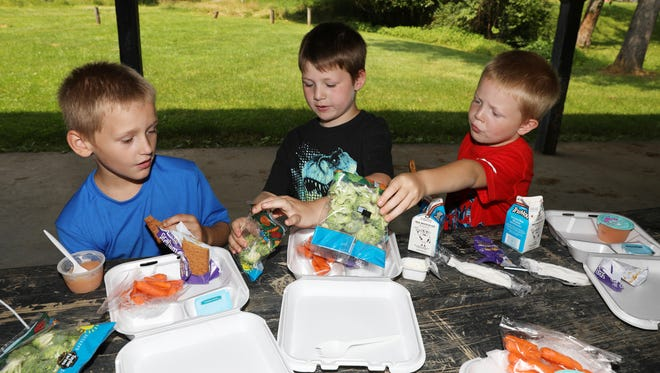 Colton Lyall, 4, offers his broccoli to Ty Early, 8, or Jorge Hickenbottom, 7, left, at Merrick Park in Zanesville. The trio were taking advantage of Zanesville City School's summer lunches program.