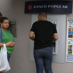 People use a Banco Popular ATM machine a day after Puerto Rican Governor Alejandro Garcia Padilla gave a televised speech regarding the governments $72 billion debt on June 30, 2015 in San Juan, Puerto Rico.