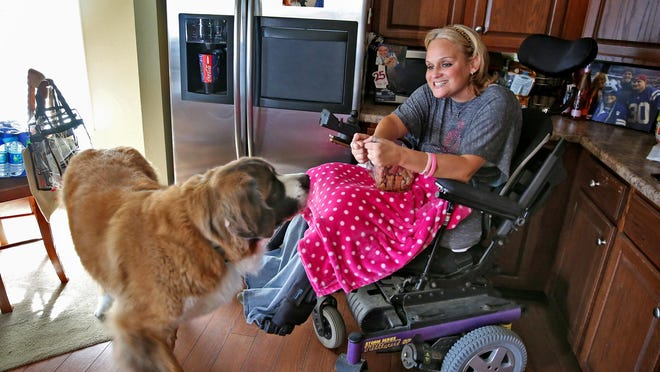 Nicole Richards gives treats to her St. Bernard dog Karolyi at her home in Greenwood. After a devastating accident that ended her gymnastics career, she was diagnosed with breast cancer.