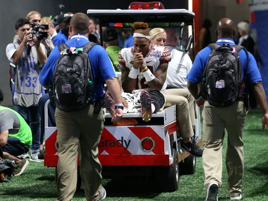 FSU's Deondre Francois is helped off of the field after injuring his leg in their 24-7 loss to Alabama at the Mercedes-Benz Stadium on Saturday, Sept. 2, 2017.