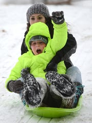 Sheva Laird and her son, Levi, enjoy the new snow sledding