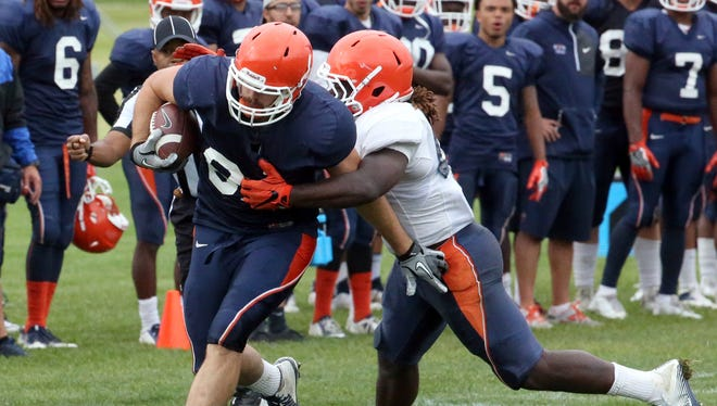 UTEP tight end Sterling Napier, 81, is brought down by linebacker Jamar Smith, 45, on Sunday at Camp Ruidoso.