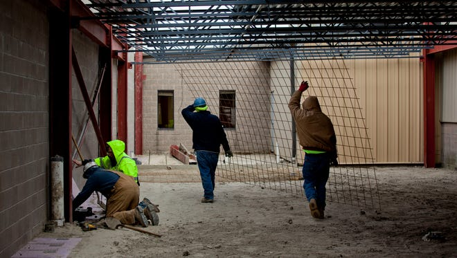 Workers carry a wire mesh as they prepare the foundation of a 15,000-square-foot addition Tuesday at SMR Automotive Systems, 1855 Busha Highway.