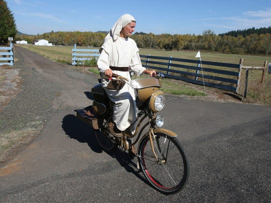 Cheryl Cutler rides a bike that she built herself from old bike parts, recycled mobile home siding and kitchen pots near Lorane, Ore.