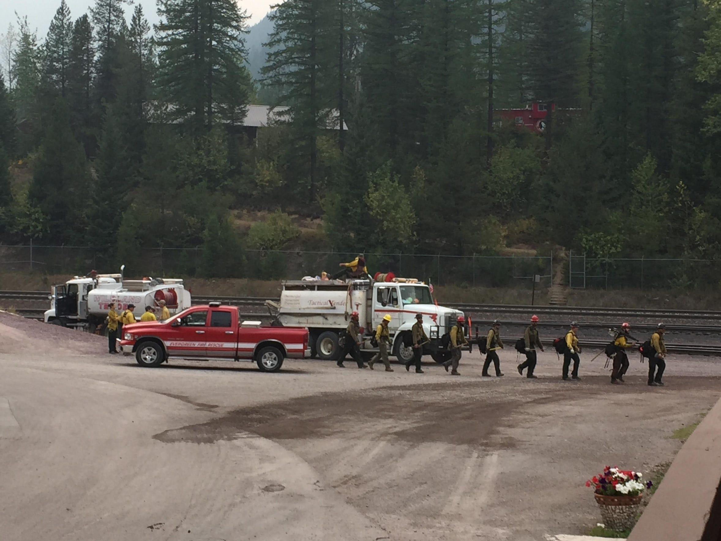 Firefighters walk in front of the Izaak Walton Inn.