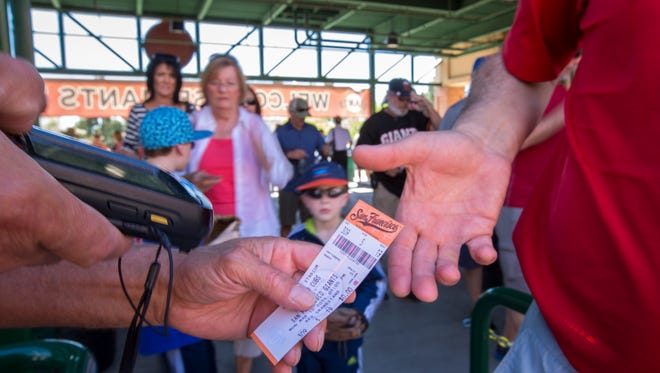 A ticket taker at Scottsdale Stadium works a Cactus League baseball game between the San Francisco Giants and the Chicago Cubs.