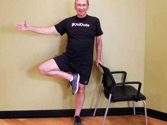 Jack Lofte shows the yoga tree pose with chair assist