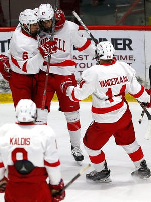 Anthony Angello, center, is greeted by teammates Alex Green, left, and Mitch Vanderlaan following a goal against Princeton at Lynah Rink on Jan. 5. The Big Red are unbeaten in 10 straight games.
