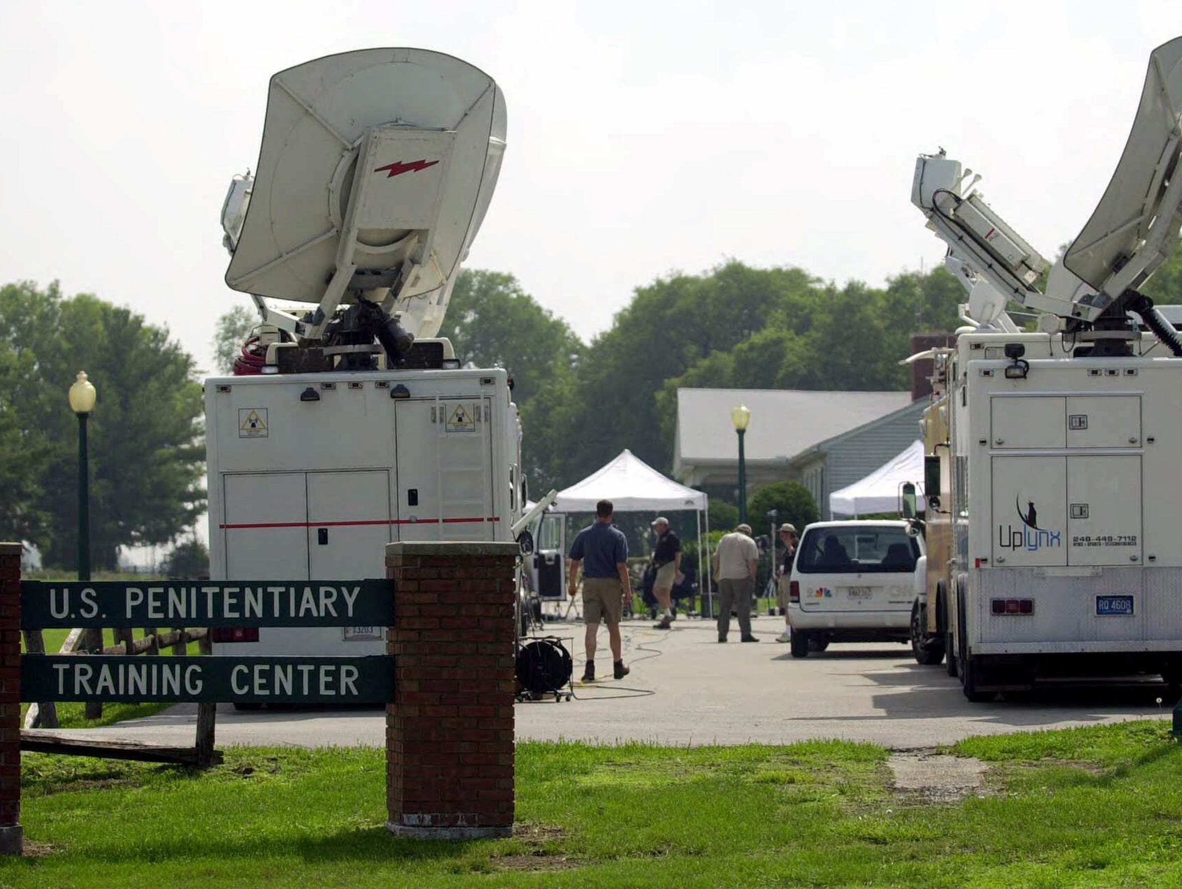 Satellite trucks arrive in the parking lot of the federal