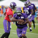 Minnesota Vikings quarterback Teddy Bridgewater, left, hands off to running back Adrian Peterson during practice at an NFL football training camp on the campus of Minnesota State University Sunday, July 26, 2015, in Mankato, Minn. (AP Photo/Charles Rex Arbogast)