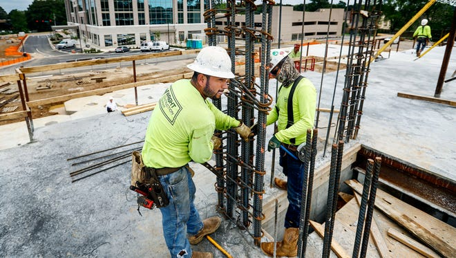 Wright Construction Company employees Julio Morano (left) and Alvaro Gomez (right) bend rebar poles while working on a new hotel that is under-construction and apart of the TruVure development in Germantown.